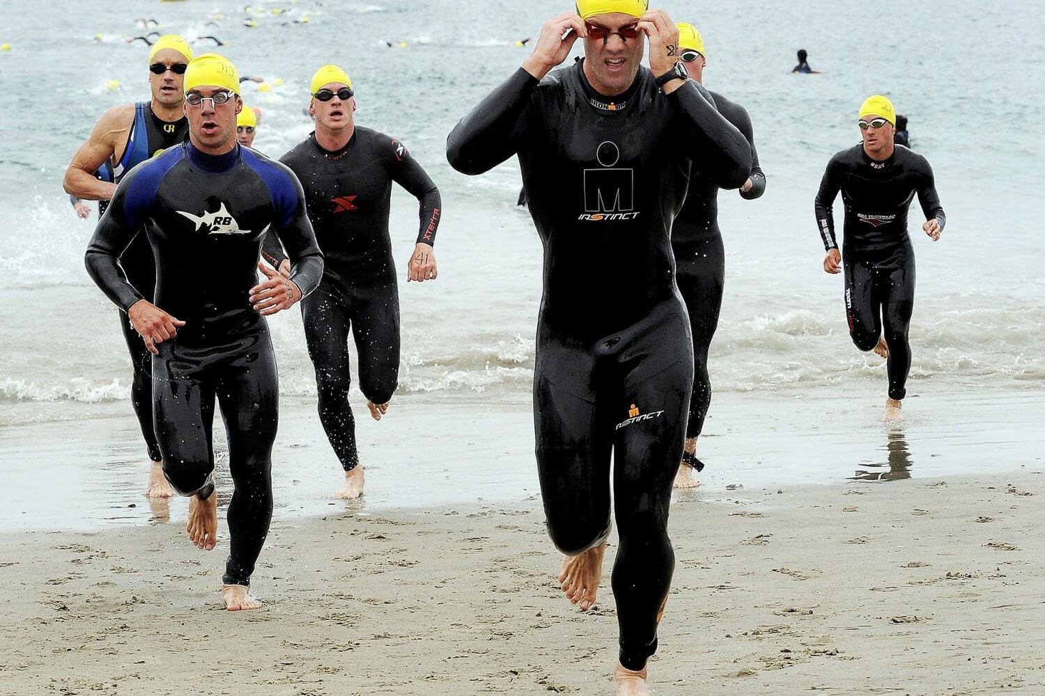 men running out of the sea in a triathlon race
